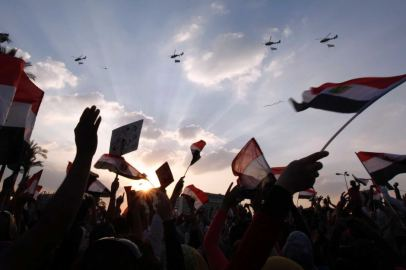 Egyptian army helicopters hoisting the national flag fly over demonstrators on Tahrr Square.