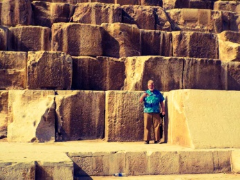 Sam standing among the collosal, ancient limstone blocks that were used to build the Great Pyramid of Pharaoh Khufu.
