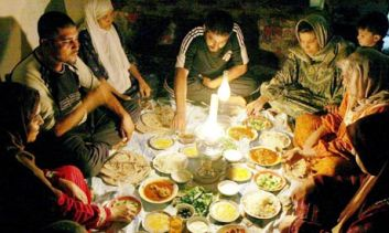 A Muslim family breaks the fast at sundown with Iftar.