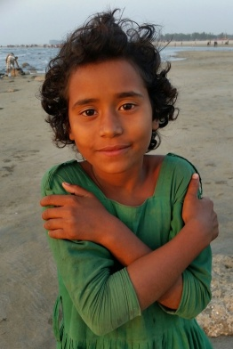 A young Rohingya girl mingles along with tourists on a beach looking for ways to make money.