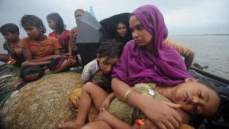 A Rohingya mother holds her child close as she flees persecution by boat.